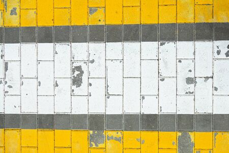 Shabby yellow and white Road marking Warning crosswalk on grey tile