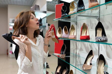 Interested woman holding black heeled shoe and red defocused heeled shoe in shop. Photo with depth of field