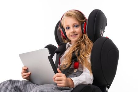 A little girl with makeup and long blonde hair sitting in a car baby chair with tablet, earphones, listen to music and chatting with friends. Stock Photo