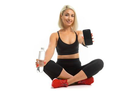 Beauiful sport caucasian girl sits on floor in res sneakers, cross legs, shows a mobile phone and keeps a bottle of water isolated on white background.