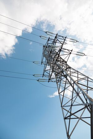 High electricity pylon against sky and clouds. Vertical image
