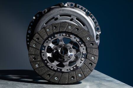 Close-up picture of a part of car, black clutch disk isolated on black background.