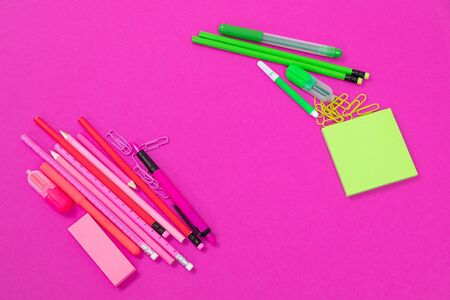 Two groups of pink and bright green office supplies are lying in opposite corners on pink background isolated