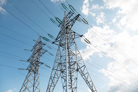Botton view of transmission towers against azure sky Stockfoto