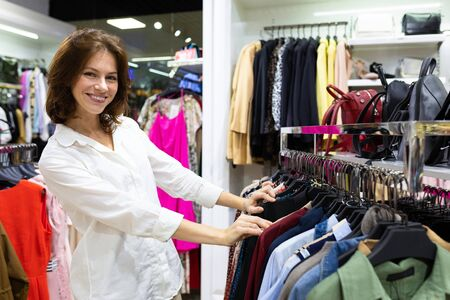 Female shop assistant in white shirt helps to buy clothing in shirt department. Stockfoto