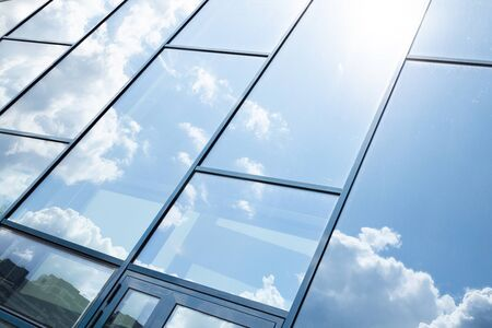 Glass building facade with blue sky reflection. Banque d'images