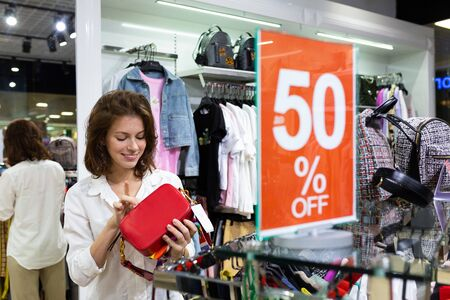 Caucasian woman holding bright red purse bag in her hand with beautiful smile. Sale season sign.