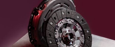 Panorama of spare part - clutch plate against maroon background. Photo with depth of field