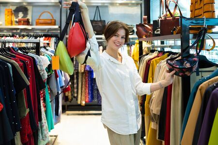 Tall caucasian woman holds colourful belt bags in showroom 免版税图像