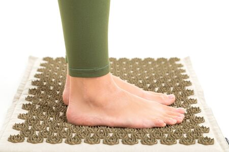 Female feets without shoes stands on a sports mat, profil