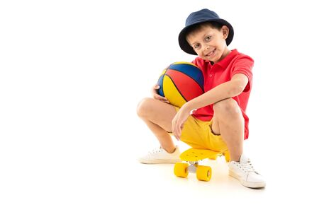 Caucasian teenager boy sits on a yellow penny with ball and smiles.