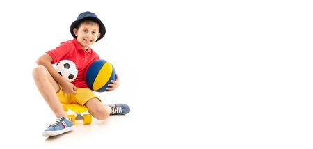 Caucasian teenager boy sits on a yellow penny with basketball and soccer balls and smiles. Banco de Imagens
