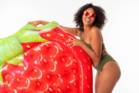 Pretty african female stands in swimsuit with rubber beach strawberry mattress and smiles isolated on white background. Banco de Imagens