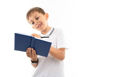 Portrait of a little caucasian boy writting something in notebook and smiles.
