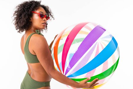 Pretty african female in swimsuit stands with big colourful rubber ball isolated on white background. Banco de Imagens - 133679368