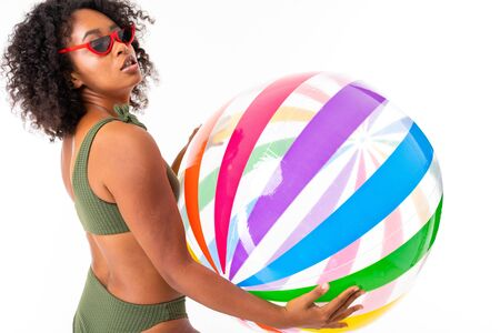 Pretty african female in swimsuit stands with big colourful rubber ball isolated on white background.