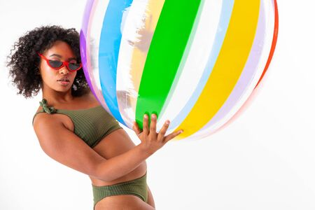 Pretty african female in swimsuit stands with big colourful rubber ball isolated on white background. Banco de Imagens - 133679380