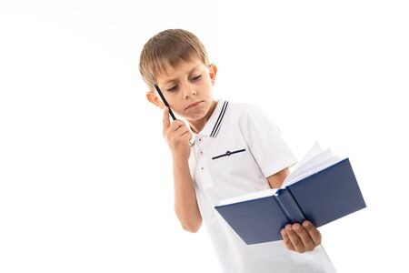 Portrait of a little caucasian boy in doubhts writting something in notebook and think Banco de Imagens