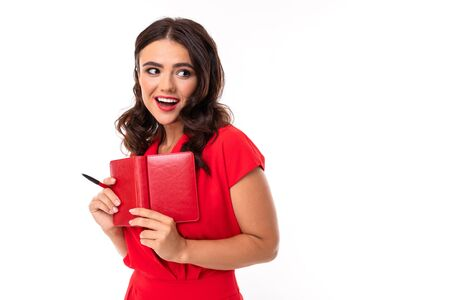 A young woman with bright makeup, in a red summer dress stands with a notebook and smiles. Banco de Imagens - 133679394