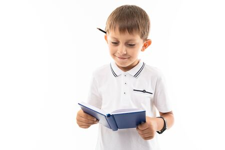 Portrait of a little caucasian boy in doubhts writting something in notebook and think.