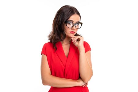 A young woman with bright makeup, in a red summer dress stands with a glasses and think about something serious.