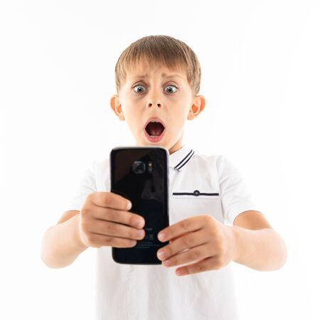 Portrait of happy caucasian boy chatting with his friends or playing phone games and is surprised. Banco de Imagens
