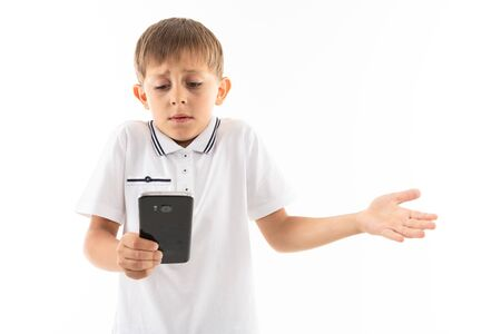 Portrait of happy caucasian boy chatting with his friends or playing phone games and unhappy.