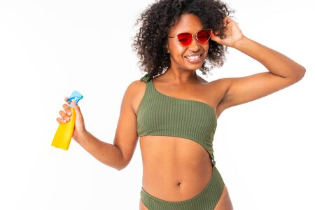 Pretty african female in swimsuit with spay can and smiles isolated on white background. Banco de Imagens