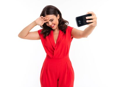 A young woman with bright makeup, in a red summer dress stands with a phone in hand.