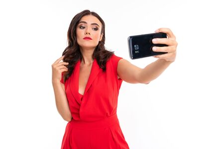 A young woman with bright makeup, in a red summer dress stands with a phone in hand. Banco de Imagens - 133679450