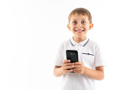 Portrait of happy caucasian boy chatting with his friends or playing phone games, wins and smiles.