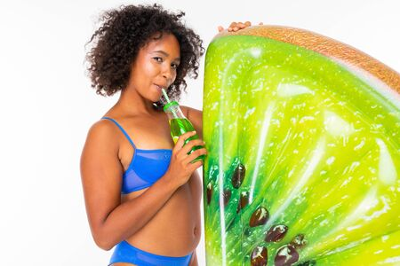 Pretty african female stands in swimsuit with rubber beach kiwi mattress, drinks juice and smiles isolated on white background.