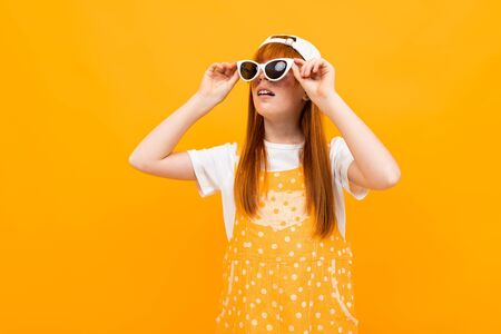 red-haired girl in sunglasses grimaces at the camera on a yellow background.