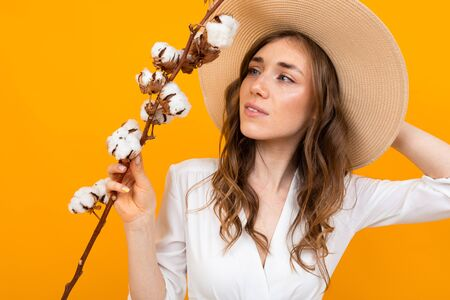 beautiful girl with a summer hat holding a sprig of cotton in his hand on a yellow background.