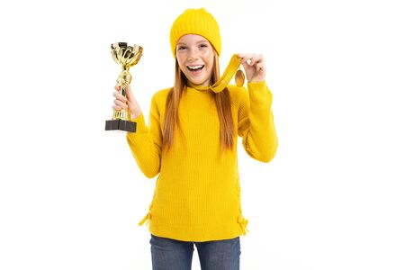 Happy red-haired girl holding a cup and a gold medal on a white background.