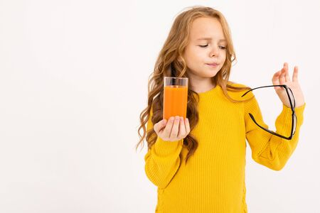 attractive european girl took off her glasses and holds a glass of carrot juice in her hand on a white background.