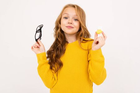 pretty young girl holding a container for lenses and glasses in his hand on a white studio background.
