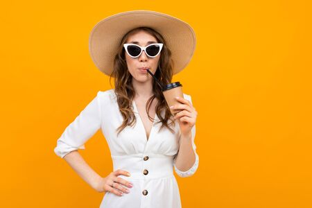girl dressed in a white dress with a hat i in glasses drinks a drink on a yellow background. Banco de Imagens