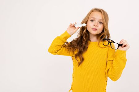 girl holds eye drops and glasses on a white studio background.