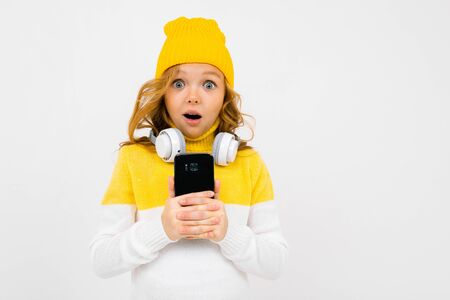 European cute girl with big headphones and smartphone listens to music and grimaces on a white studio background.