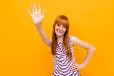 red-haired smiling beautiful girl in a T-shirt grimaces looking at the camera over yellow colorful background.