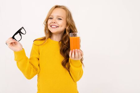smiling european girl took off her glasses and holds a glass of carrot juice in her hand on a white background.