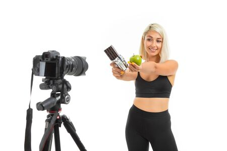 athletic girl in a sports uniform shows apples and chocolate on a camera on a white background. Zdjęcie Seryjne