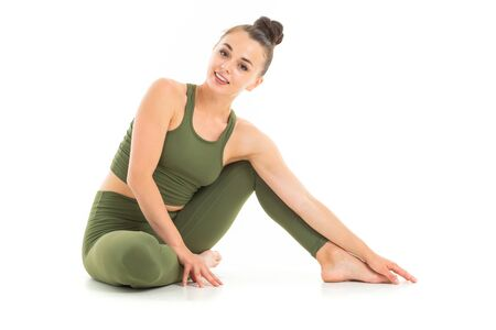 European brunette girl in a green sports suit does yoga on a white background.