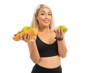 sports girl in a sports uniform shows an apple and fast food on a camera on a white background.