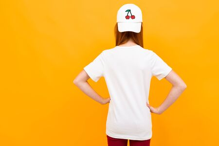 smiling european red-haired girl in a white t-shirt stands with her back on a yellow background