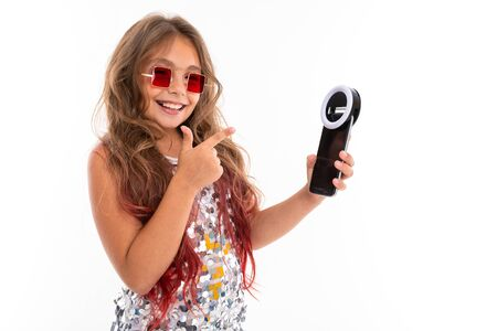 Little pretty caucasian girl do selfie with phone and circle lamp, picture isolated on white background.