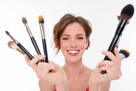 Portrait of young beautiful girl show her makeup brushes isolated on white background. Zdjęcie Seryjne