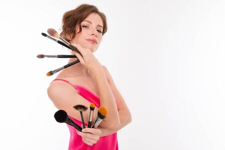 Young beautiful girl show her makeup brushes isolated on white background.