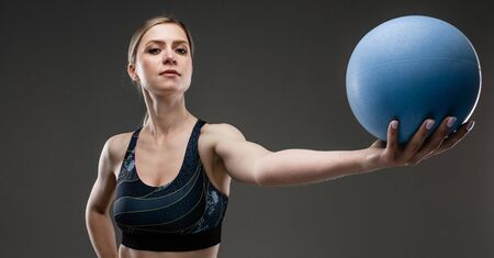 Sport caucasian girl with slim figure do exercises with blue ball isolated on black background.